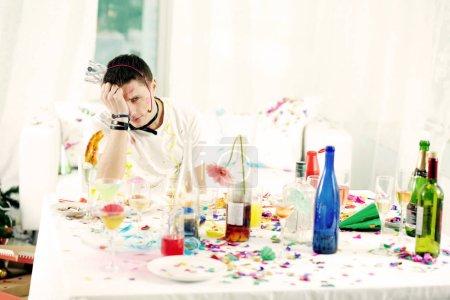 Photo pour Jeune homme assis à la table désordonnée après la fête turbulente - image libre de droit
