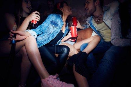 Photo pour Mouchard angle faible tir de fêtards jeune moderne, groupe de filles et l'homme, assis sur un canapé en réfrigération salon du club sombre, boire de la bière et soufflant vape fume vers d'autres bouche - image libre de droit