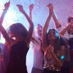 Ecstatic friends dancing in confetti rain...