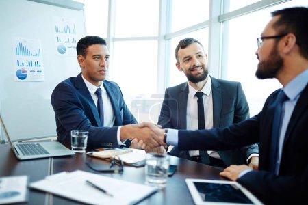 Business partners handshaking after negotiations