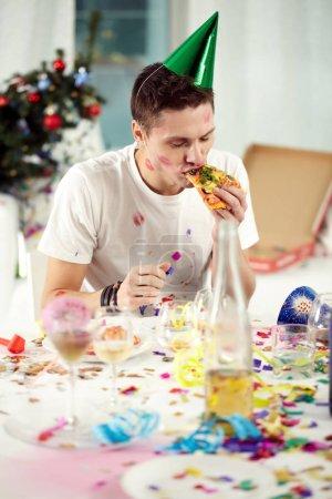 Photo pour Jeune homme ivre mangeant le dernier morceau de pizza après une nuit rugissante - image libre de droit