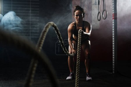Sporty woman pulling ropes at gym