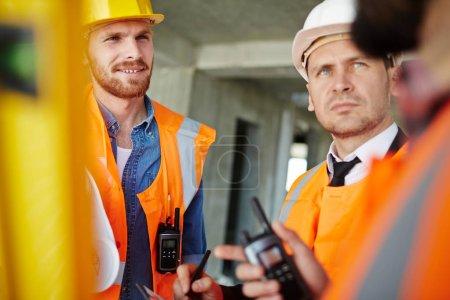 Photo pour Inspecteurs de biens immobiliers ayant conversation sur chantier - image libre de droit