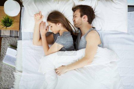 Tired couple sleeping under blanket