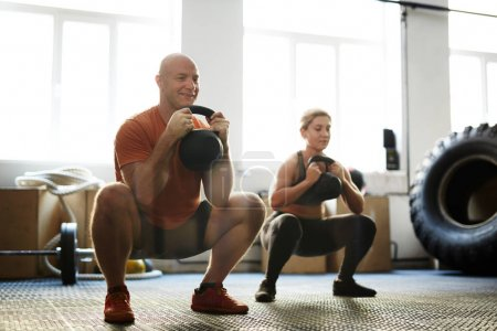 Photo for Strong man and woman squatting while exercising with kettle bells - Royalty Free Image