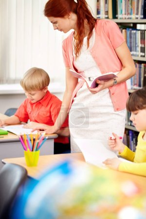teacher looking after working student