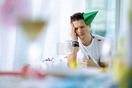 Photo pour Portrait de jeune homme avec une mauvaise tête après la fête - image libre de droit