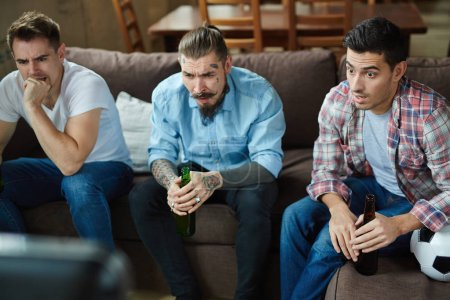Photo for Nervous guys watching tv broadcast of football match - Royalty Free Image