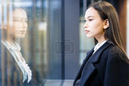 Young employee looking through window