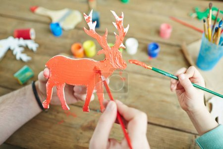 Wooden deer figure being painted by gouache