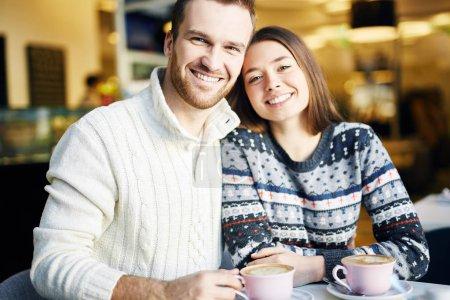Happy couple having cappuccino