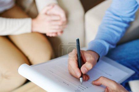 Hand of psychologist over medical card
