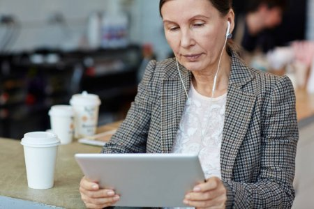 Businesswoman with earphones using touchpad