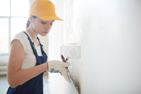 Female repairperson carrying out plasterwork