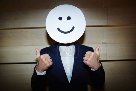 Businessman covered face with smiling mask