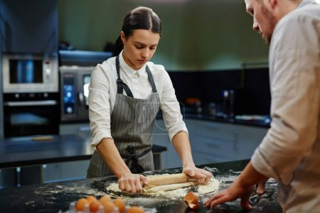 Photo for Female trainee rolling fresh dough with chief near by - Royalty Free Image