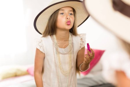 little girl with lipstick looking at mirror