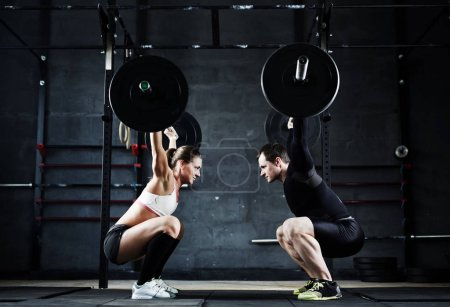 man and woman holding huge heavy barbells