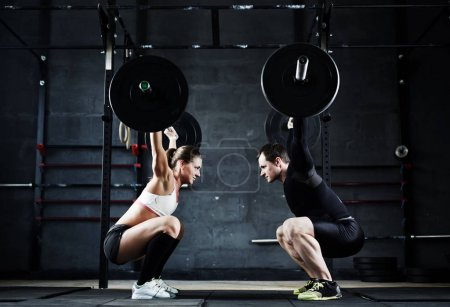 Photo for Motivational wide shot of young man and woman holding huge heavy barbells overhead looking at each other - Royalty Free Image