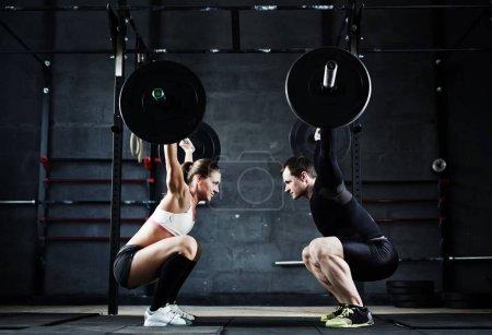 Photo pour Motivationnel plan large de jeune homme et femme tenant d'énormes lourdes cloches au-dessus de la tête en regardant les uns les autres - image libre de droit