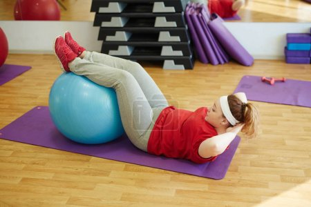 Woman using fitness ball for sit ups