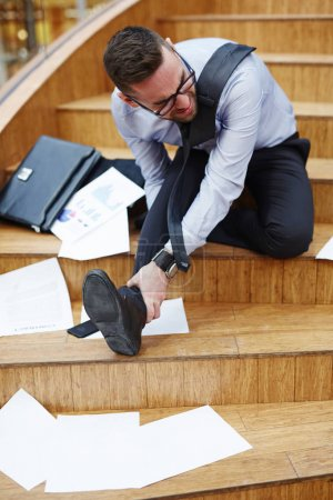 Businessman fell down on stairscase...