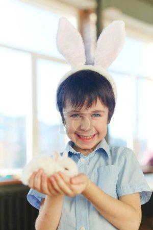 Smiling boy with white rabbit