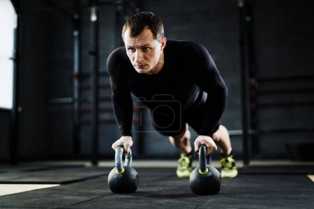Man performing kettlebell pushups