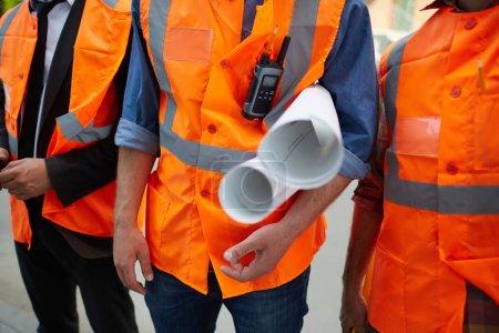Photo pour Plan rapproché de trois travailleurs de la construction méconnaissables portant des gilets réfléchissants orange debout sur le site tenant des plans de construction - image libre de droit