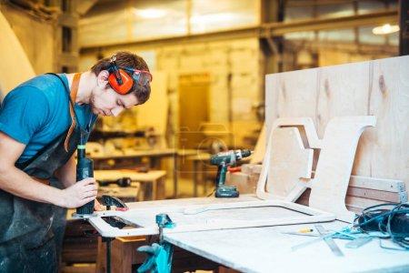 Cabinetmaker grinding workpiece