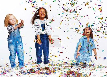 Foto de Retrato de estudio de niños sobre fondo blanco: tres niñas alegres todas vestidas con ropa vaquera azul divirtiéndose lanzando confeti de papel de aluminio al aire y viéndolo caer en destellos - Imagen libre de derechos