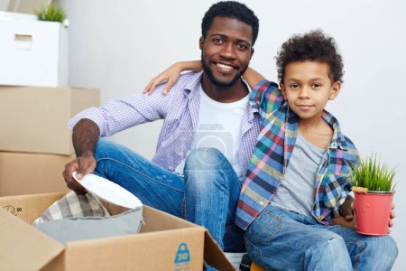 Photo for Little son and his father unpacking things from carton box - Royalty Free Image