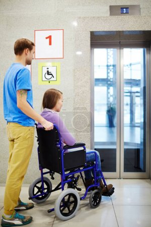 Woman in wheelchair and assistant