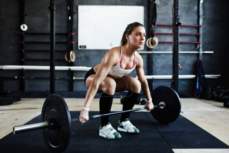 woman ready to pick up barbell