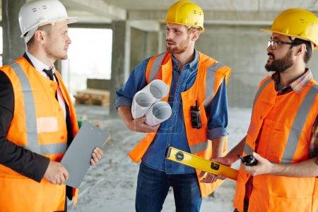 Photo pour Groupe de trois ouvriers portant casques et gilets debout parmi des murs de béton sur chantier, discuter des progrès du développement avec inspecteur, outils et plans - image libre de droit