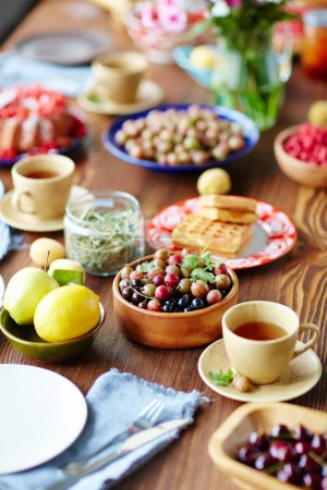 Photo for Breakfast table setting full of gooseberries and currant, fruits, freshly baked waffles and cups of scented tea - Royalty Free Image