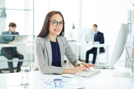 Photo pour Portrait de jeune analyste d'affaires asiatique tapant à l'ordinateur moderne assis à son lieu de travail dans un bureau léger avec un document statistique à côté d'elle - image libre de droit