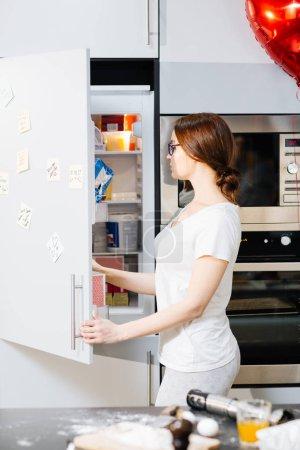 housewife taking something in refrigerator