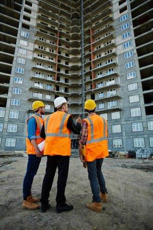 Photo pour Portrait arrière de trois ouvriers portant des gilets réfléchissants orange et des casquettes debout sur le chantier de construction contre un immeuble d'habitation inachevé, en discutant - image libre de droit