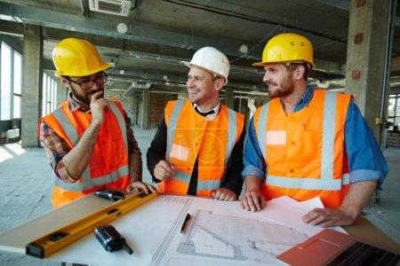 Photo pour Équipe de travailleurs de la construction joyeux portant des casques et des gilets de protection souriant et riant tout en discutant des détails du projet - image libre de droit