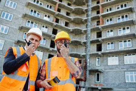 Photo pour Portrait de deux ouvriers portant des gilets réfléchissants orange et des casquettes debout à l'aide d'appareils de radio portables contre un immeuble sur le chantier de construction - image libre de droit