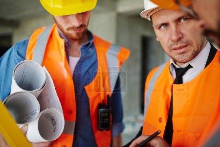 Photo pour Portrait du contremaître inspecteur parlant à deux ouvriers portant des gilets de protection et des casquettes, discutant des progrès de la construction sur place - image libre de droit