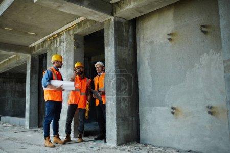 Photo pour Deux ouvriers montrant des planchers inachevés dans bâtiment de grande hauteur pour des superviseur exécutif sur chantier, tous portant des gilets orange réfléchissantes et casques - image libre de droit