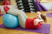 Woman using big ball for sit ups