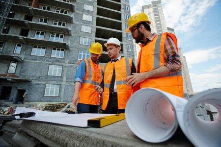 Photo pour Portrait en angle bas de deux ouvriers montrant les plans de l'immeuble à l'inspecteur sur le chantier, tous portant des gilets réfléchissants orange et des casquettes - image libre de droit