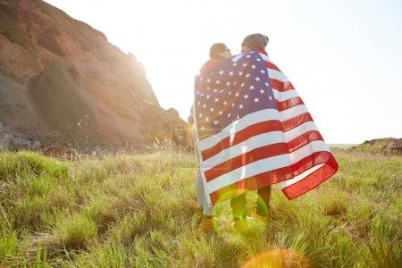proud young couple wrapped in flag