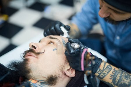 Master of tattoo art drawing on face