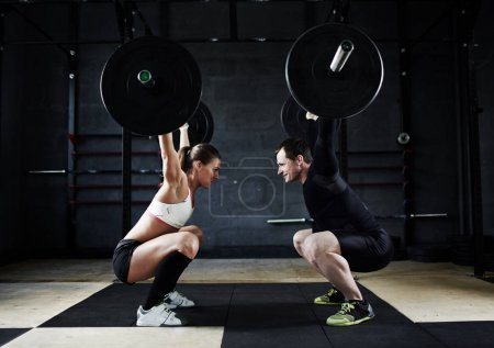 Photo for Motivational side view image of young man and woman holding  huge heavy barbells high up looking at each other - Royalty Free Image