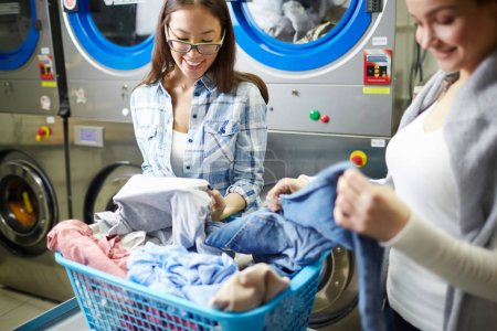 Young cheerful women talking in laundry during was...