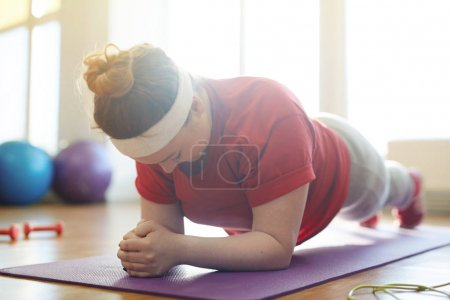 woman working out on yoa mat in studio